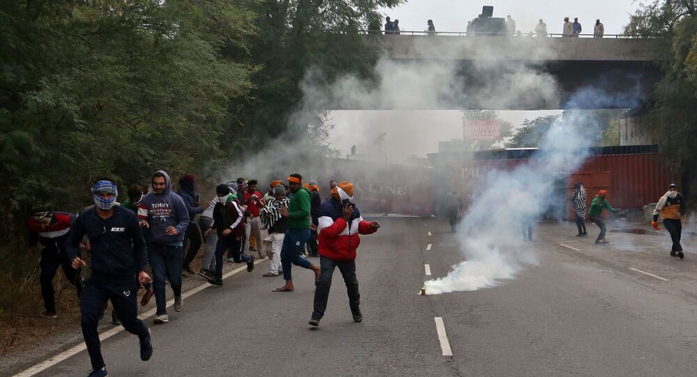 Farmers protesting against newly passed agricultural reforms flee tear gas fired by police on a national highway at Dharuhera, in the northern state of Haryana, India, 3 January 2021.