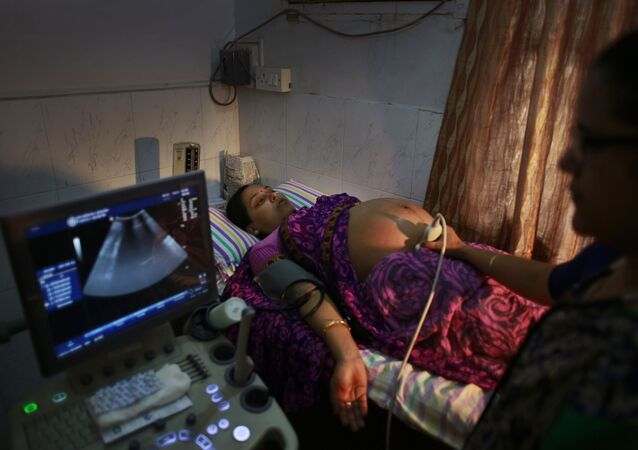 n Indian pregnant woman is examined by her gynecologist at a hospital in Gauhati, India, Friday, July 11, 2014