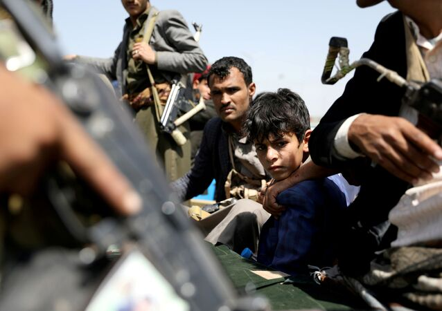 A boy rides with Houthi followers on the back of a patrol truck during the funeral of Houthi fighters