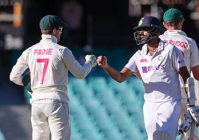 (FILES) This file photo taken on January 11, 2021 shows India's Ravichandran Ashwin (R) fist-bumping with Australia's captain Tim Paine (L) at the end of the third cricket Test match between Australia and India at the Sydney Cricket Ground (SCG) in Sydney.