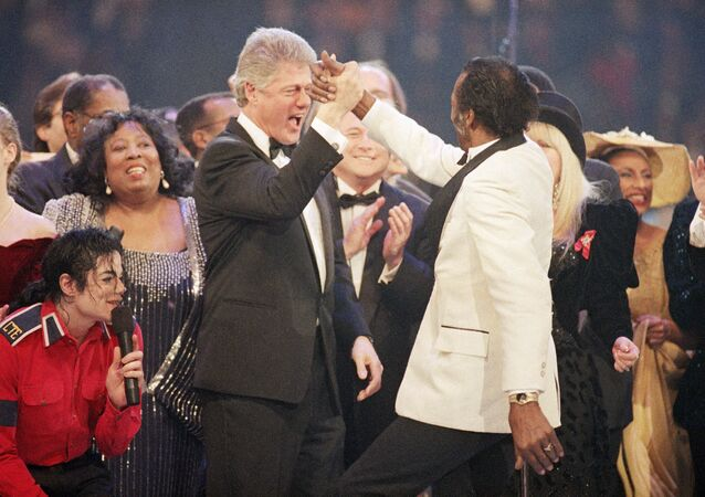 Bill Clinton, left centre, gives a high five to Chuck Berry, right, during the finale of the Presidential Gala at the Capital Centre in Landover, Maryland, 19 January 1993.