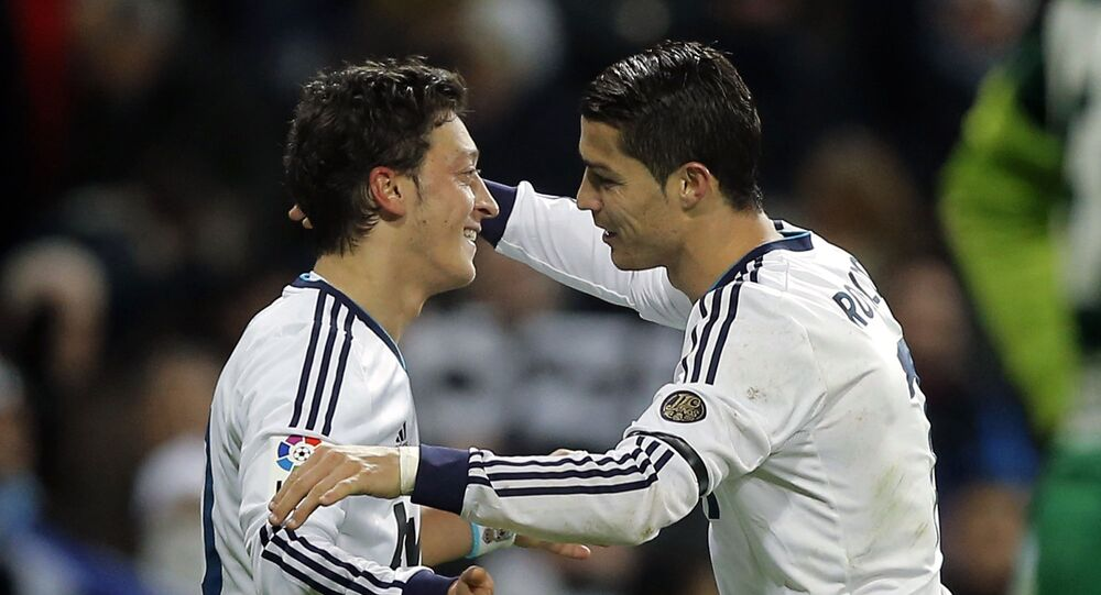 Real Madrid's Mesut Ozil from Germany, left, celebrates with Cristiano Ronaldo from Portugal after scoring a goal against Atletico de Madrid during a Spanish La Liga football match at the Santiago Bernabeu stadium in Madrid, Saturday, 1 December 2012.