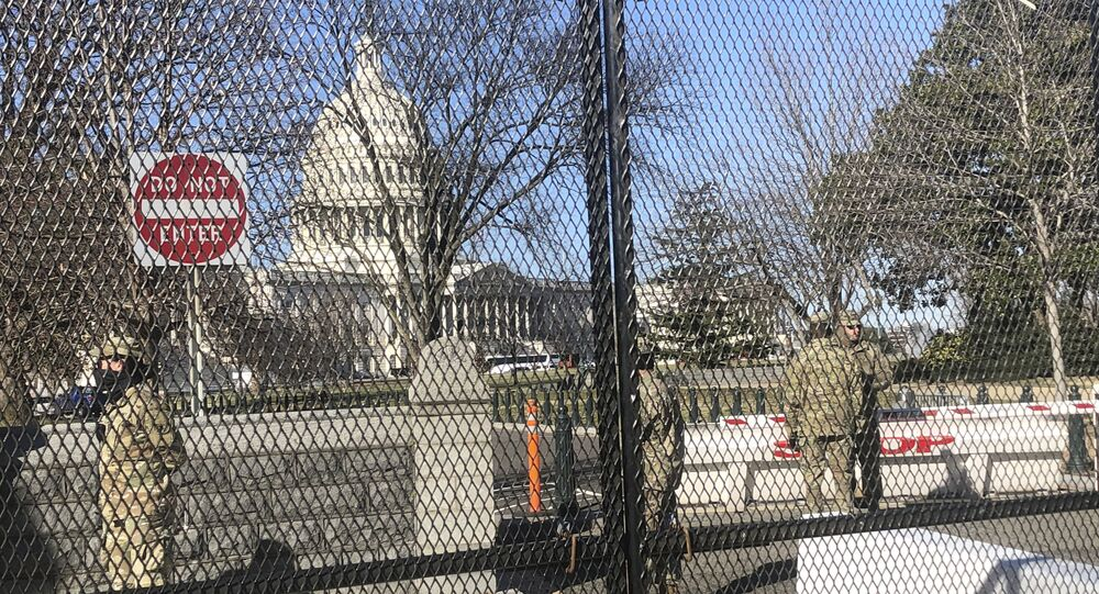 Members of the National Guard stand inside anti-scaling fencing that surrounds the Capitol, Sunday, Jan. 10, 2021, in Washington