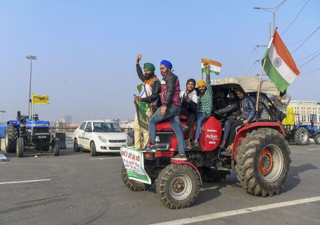 Protesting farmers shout slogans near police barricades as they continue to protest along a blocked highway against the central government's recent agricultural reforms, at the Gazipur Delhi-Uttar Pradesh state border, in Ghaziabad on January 12, 2021.