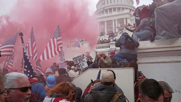 A cloud of colored smoke appears as a mob of supporters of U.S. President Donald Trump storm the U.S. Capitol Building in Washington, U.S., January 6, 2021. Picture taken January 6, 2021.  - Sputnik International