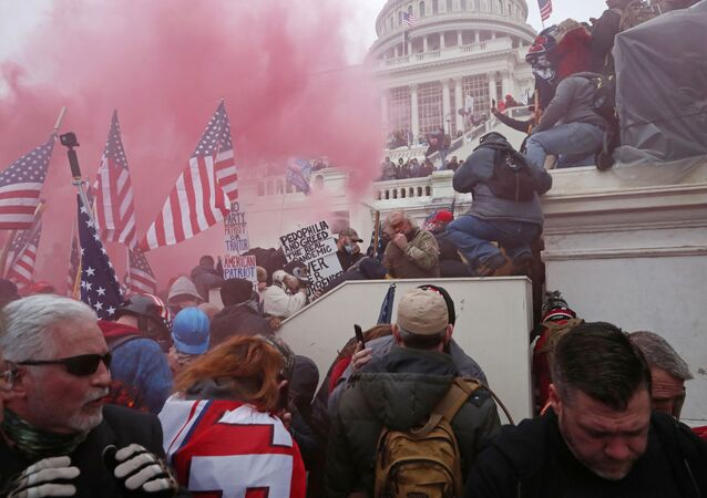 A cloud of colored smoke appears as a mob of supporters of U.S. President Donald Trump storm the U.S. Capitol Building in Washington, U.S., January 6, 2021. Picture taken January 6, 2021.