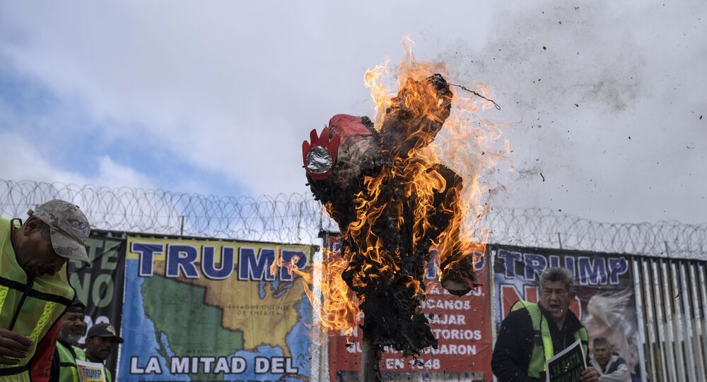 A pinata depicting US President Donald Trump is burned by members of Border Angels and Alianza Migrante during a demonstration
