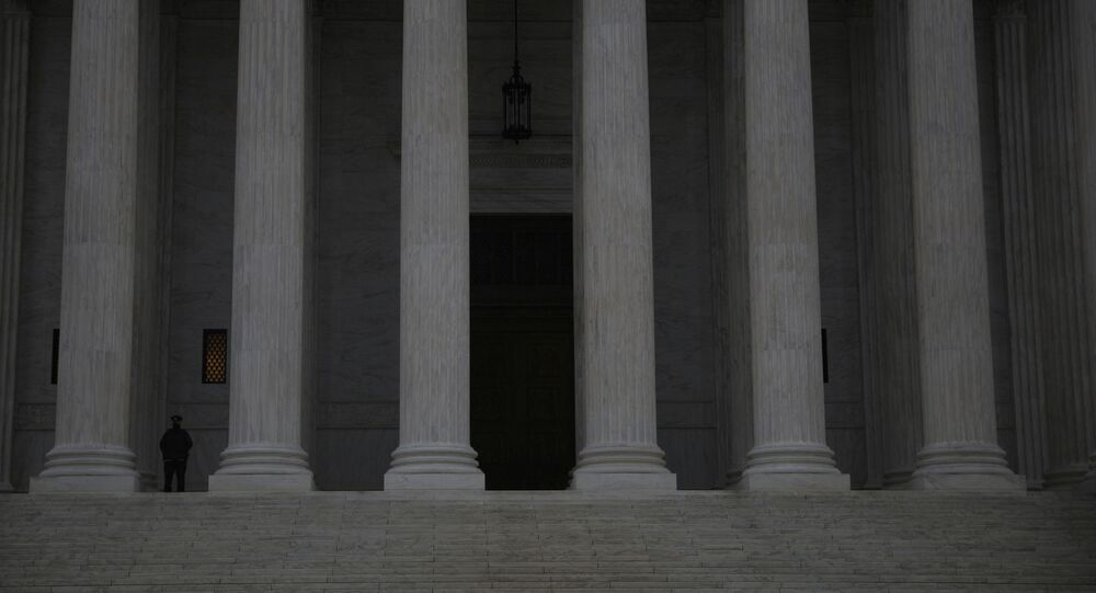 A United States Supreme Court Police Officer stands guard at the steps of the the United States Supreme Court