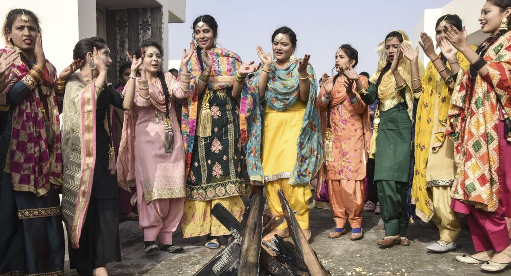 Students in traditional Punjabi dress perform the giddha folk dance around a bonfire on the eve of the Lohri festival in Amritsar on 12 January 2021.