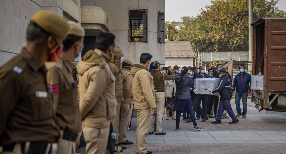Policemen stand guard as health workers shift a box containing COVID-19 vaccine from a vehicle to a cold storage at Rajiv Gandhi Super Speciality hospital in New Delhi, India, Tuesday, Jan. 12, 2021