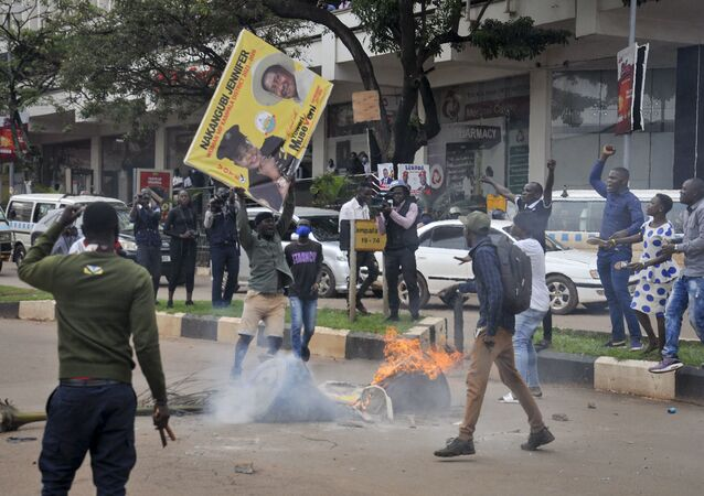 A protester supporting opposition presidential candidate Bobi Wine prepares to burn a placard showing President Yoweri Museveni.
