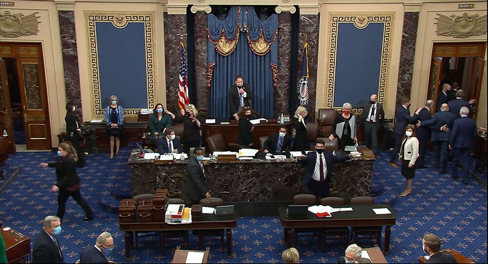 In this image from video, lawmakers evacuate the Senate floor as protesters gain entry into the U.S. Capitol on Wednesday, Jan. 6, 2021. (Senate Television via AP)