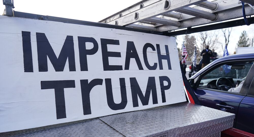 A sign stands in the box of a pickup truck during a gathering calling for the impeachment of President Donald Trump at South High School before a car rally through the streets of downtown Sunday, 10 January 2021, in Denver.
