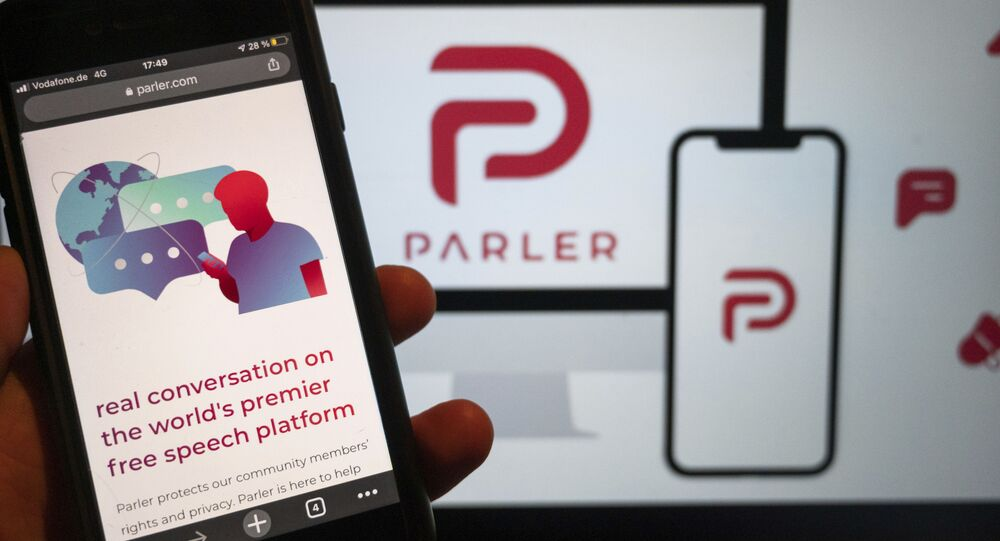 The website of the social media platform Parler is displayed in Berlin, Jan. 10, 2021. The platform's logo is on a screen in the background. The conservative-friendly social network Parler was booted off the internet Monday, Jan. 11, over ties to last week's siege on the U.S. Capitol, but not before hackers made off with an archive of its posts, including any that might have helped organize or document the riot.