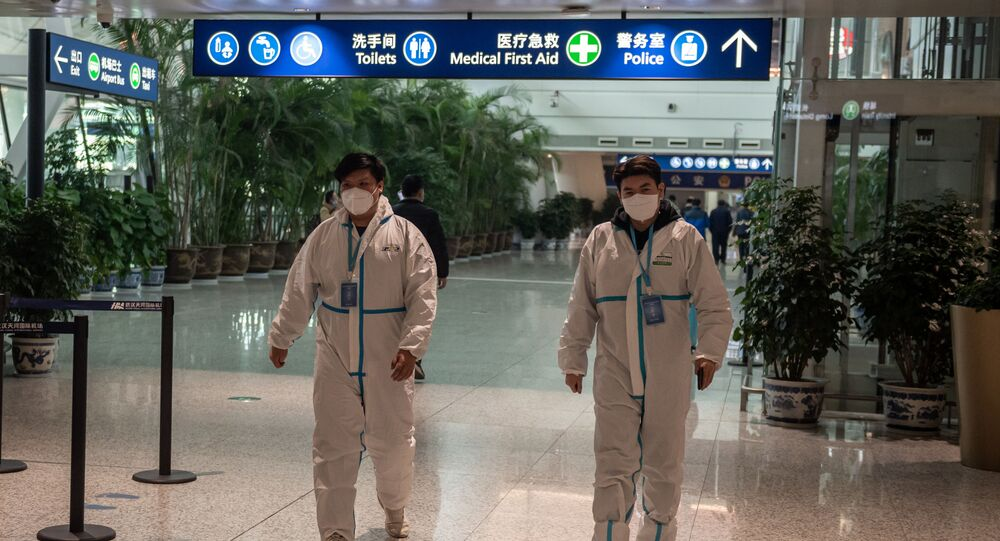 Health workers in suits walk in the international arrivals area, where arriving travellers are to be taken into quarantine, at the international airport in Wuhan on 14 January 2021, ahead of the expected arrival of a World Health Organisation (WHO) team investigating the origins of the Covid-19 pandemic.