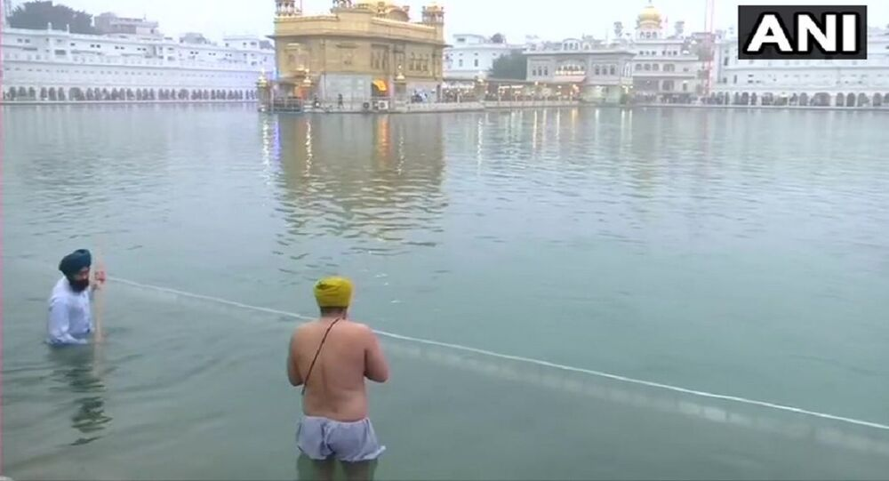Devotees take holy dip in 'Sarovar' at Golden Temple in Amritsar and offer prayers, on Maghi festival