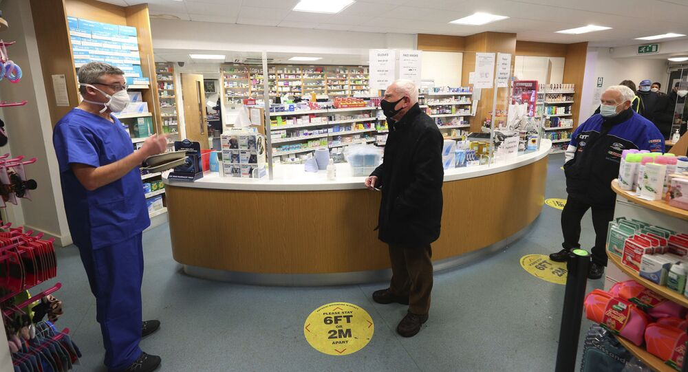 A pharmacist prepares to administer coronavirus vaccines to waiting recipients at Andrews Pharmacy in Macclesfield, England, Thursday Jan. 2021