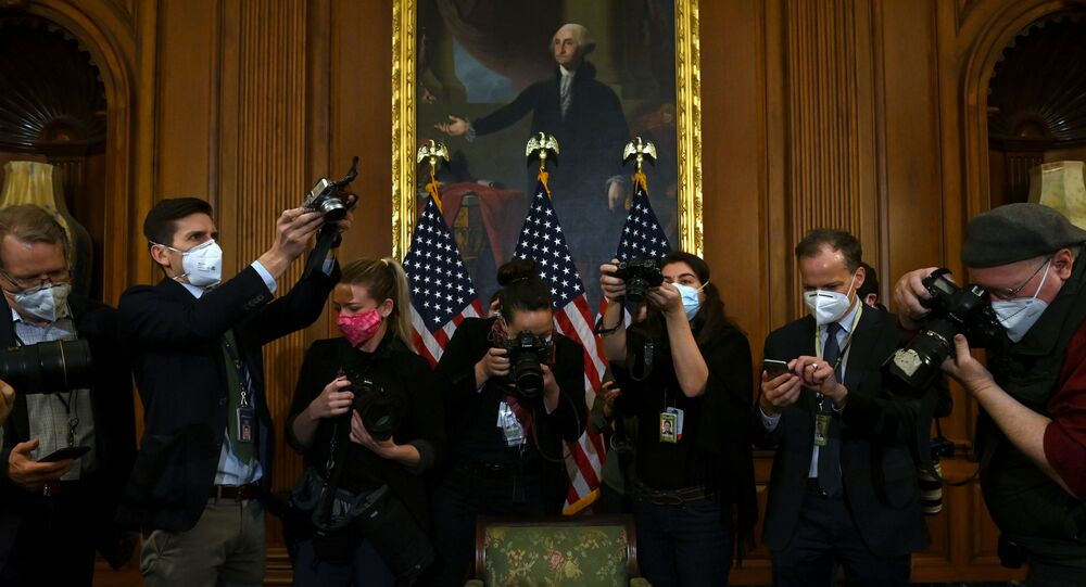 Photographers take pictures of the article of impeachment against US President Donald Trump during an engrossment ceremony after the US House of Representatives voted to impeach him at the US Capitol, 13 January 2021, in Washington, DC.