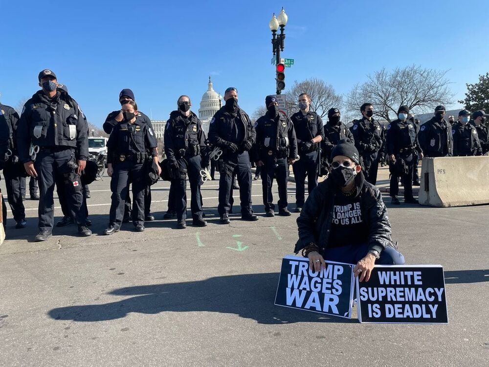 Am anti-Trump protester and police officers outside the US Capitol as the House of Representatives votes to impeach Trump.
