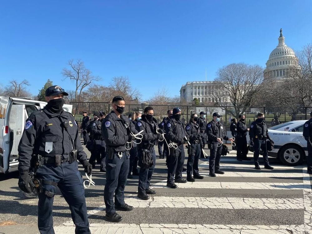 Police officers stand guard outside the US Capitol building as the House of Representatives votes to impeach Trump.