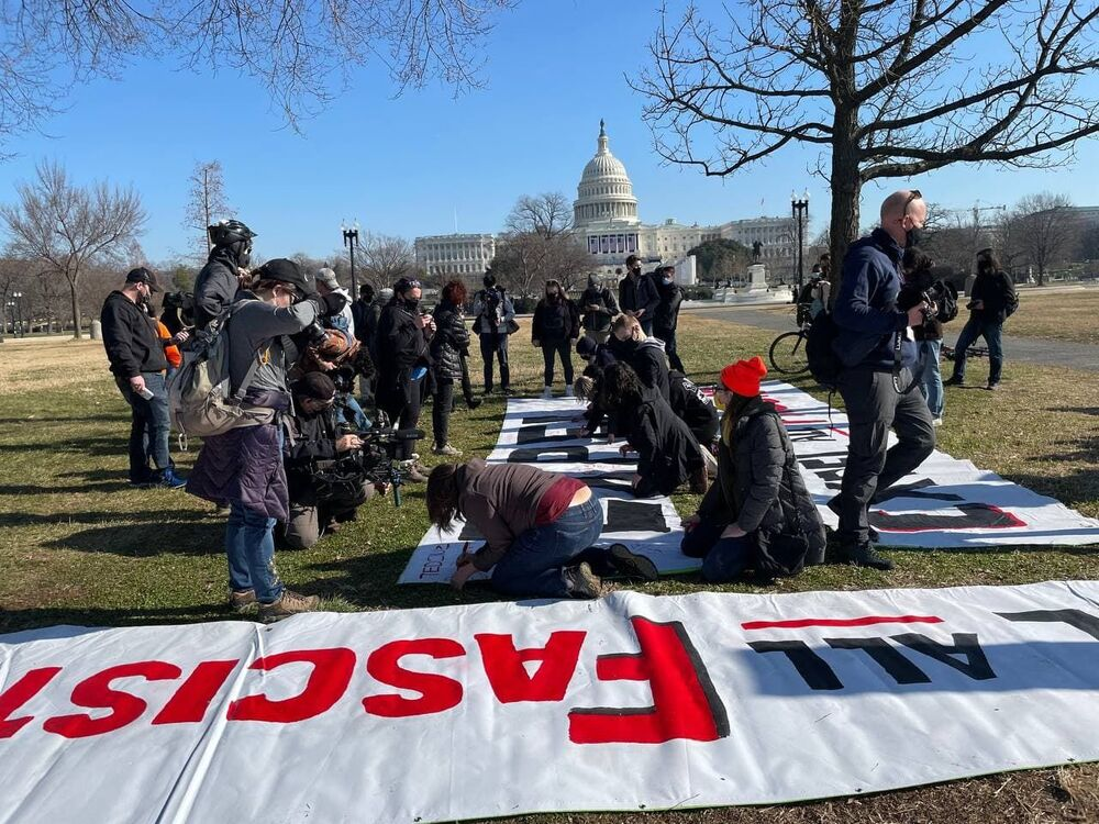Anti-Trump activists make a banner before the protest outside the US Capitol.