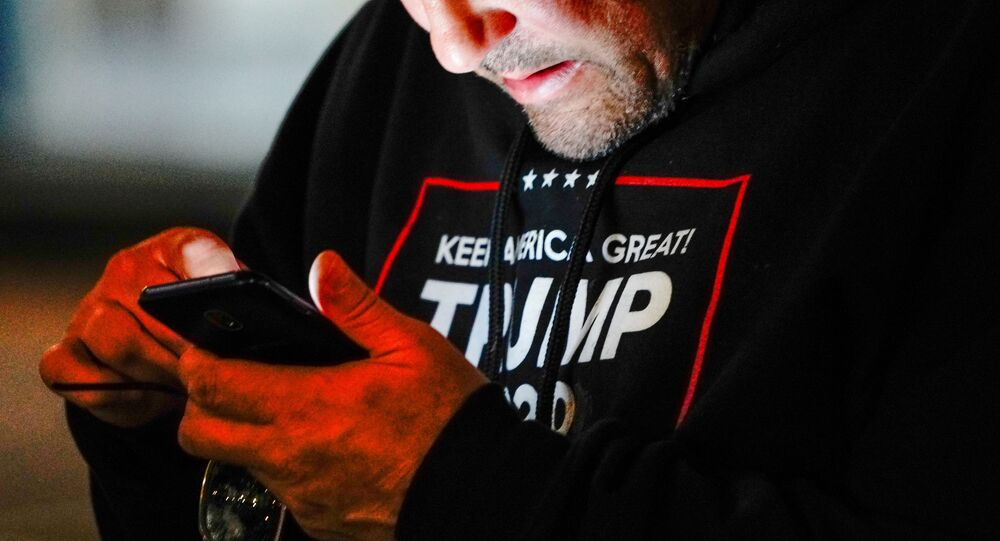 A man wearing a Trump 2020 sweatshirt uses his mobile phone during a Stop the Steal protest outside Milwaukee Central Count