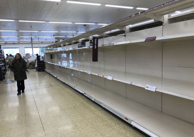 Empty shelves where toilet roll is usually stocked in a supermarket in Durham, England, Tuesday March 17, 2020, after British authorities ramped up public health measures Monday, telling people who are in the groups considered most vulnerable to severe COVID-19 illness to stay at home for three months