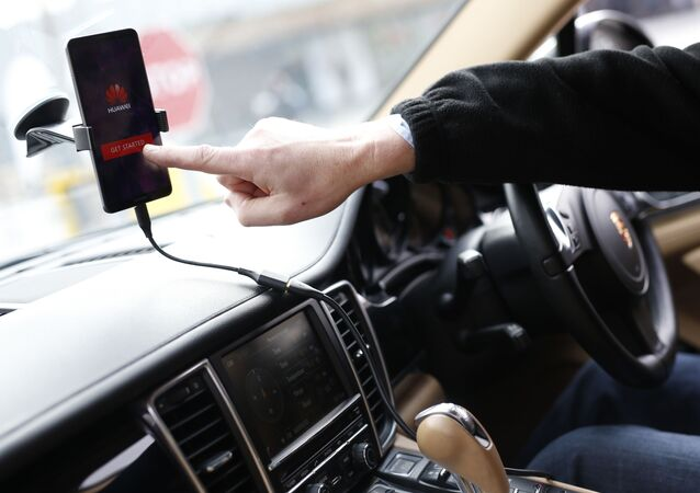 A man shows the Huawei Mate 10 Pro smartphone able to drive a Porsche Panamera car during its presentation at the Camp Nou stadium in Barcelona on February 26, 2018 on the first day of the Mobile World Congress (MWC)