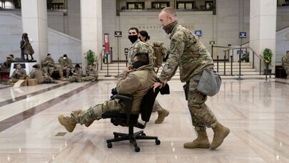 A member of the National Guard pushes a colleague in a chair through the Visitor Centre of the U.S. Capitol on 13 January 2021 in Washington, DC.
