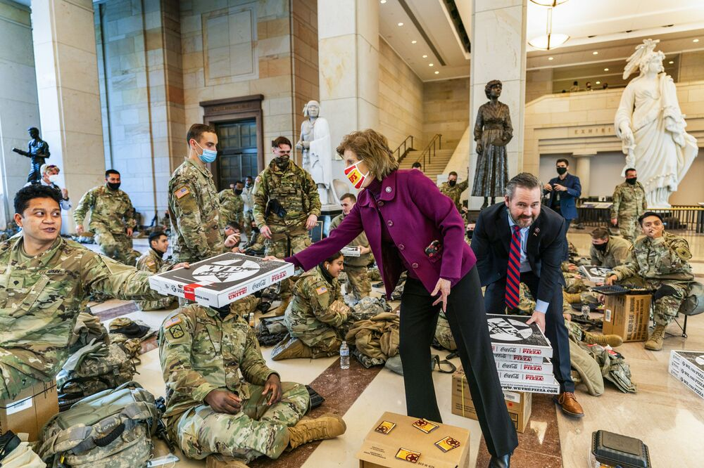 Rep. Vicky Hartzler and Rep. Michael Waltz hand pizzas to members of the National Guard gathered at the Capitol Visitor Centre, 13 January 2021 in Washington, DC.