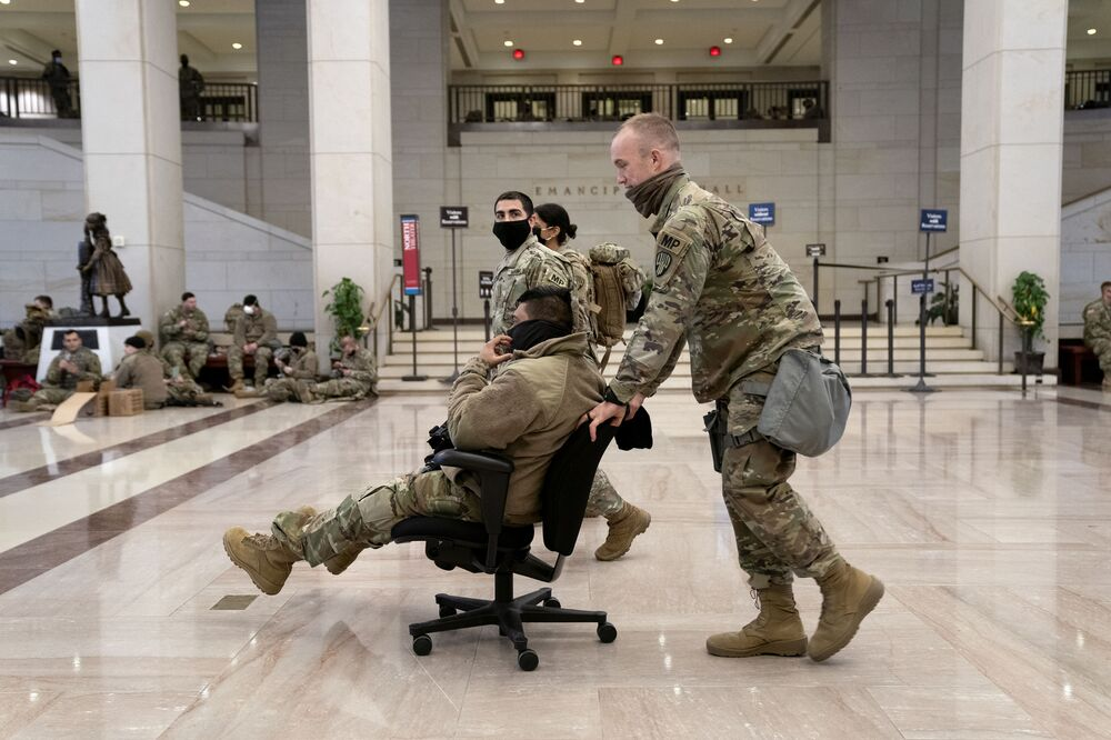 A member of the National Guard pushes a colleague in a chair through the Visitor Center of the U.S. Capitol on 13 January 2021 in Washington, DC.