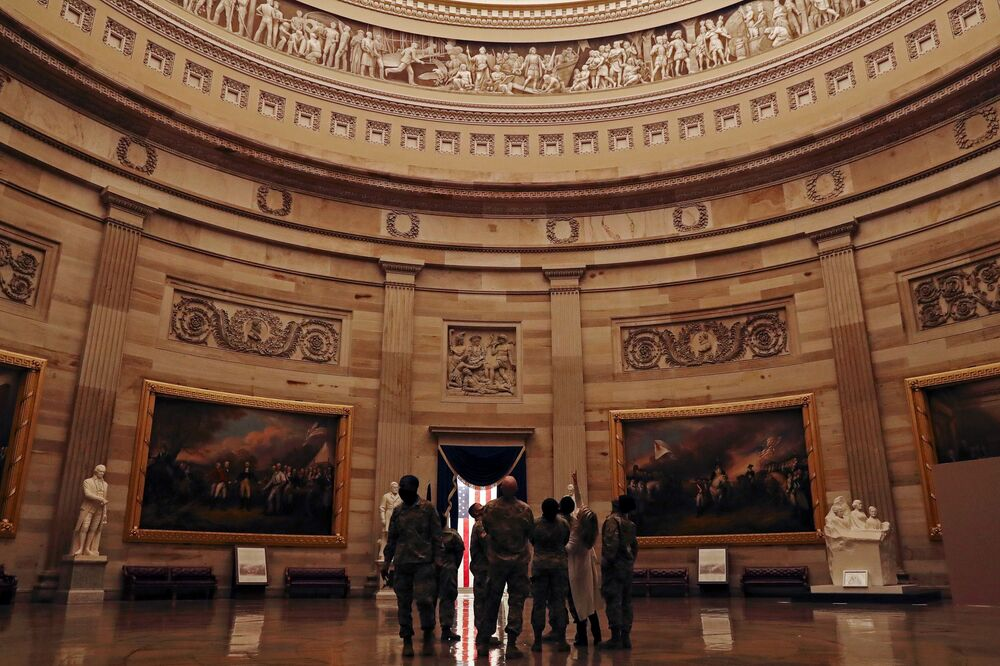Members of the National Guard look at the U.S. Capitol Rotunda in Washington 13 January 2021.