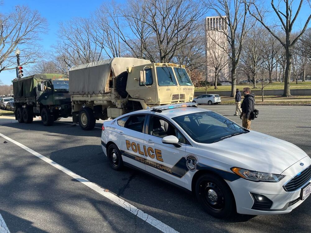 Military vehicles and a police car parked not far from the US Capitol building.