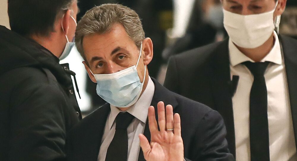 Former French President Nicolas Sarkozy waves to the media as he arrives at the courtroom in Paris, Friday, Dec. 10, 2020