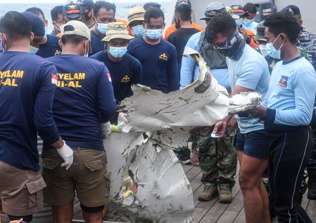Indonesian Navy members carry the remains of Sriwijaya Air plane flight SJ 182 which crashed into the sea off the Jakarta coast in Indonesia, January 13, 2021