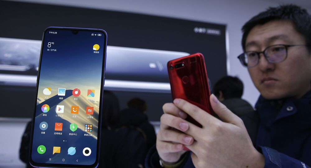 An invited guest takes a photo of Xiaomi new model Mi 9 displayed on an exhibition booth after its launch event in Beijing, Wednesday, 20 February 2019