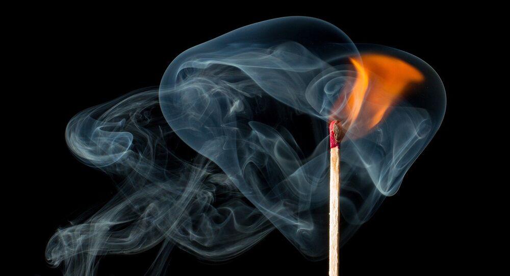 A match burns, creating a flame and smoke