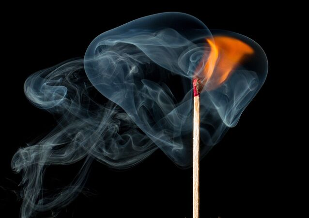 A match burns, creating a flame and smoke