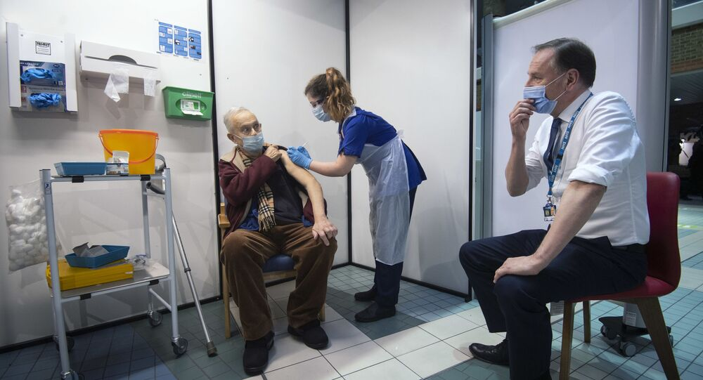 Simon Stevens (R), Chief Executive of the NHS, watches as a nurse (C) administers a dose of the Pfizer-BioNTech Covid-19 vaccine to Frank Naderer (L), 82, at Guy's Hospital in London on 8 December 2020 as the UK starts its biggest ever vaccination programme.
