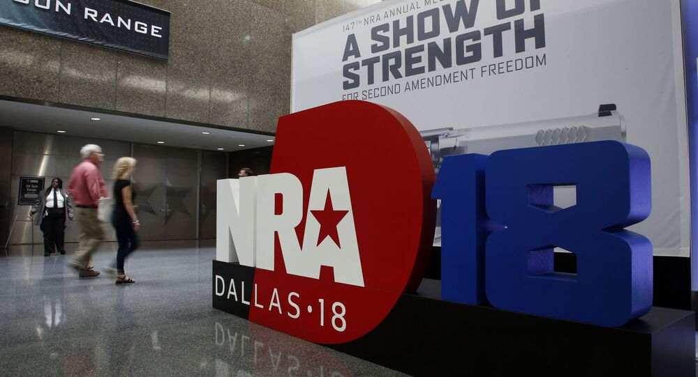 People walk by NRA convention signage in the Kay Bailey Hutchison Convention Center in Dallas, Thursday, May 3, 2018. The convention is scheduled to go through Sunday.