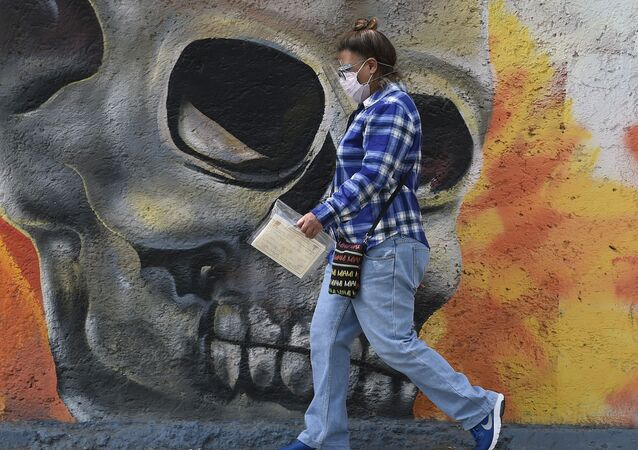A woman wearing a face mask walks past a mural showing a skull on one of the walls of the San Nicolas Tolentino cemetery in the municipality of Iztapalapa in Mexico City on January 15, 2021, amid the COVID-19 novel coronavirus pandemic.