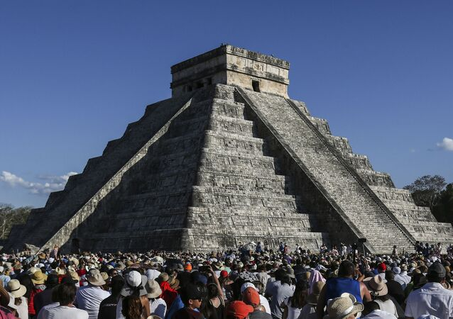 People surround the Kukulcan Pyramid at the Mayan archaeological site of Chichen Itza in Yucatan State, Mexico, during the celebration of the spring equinox on March 21, 2019.
