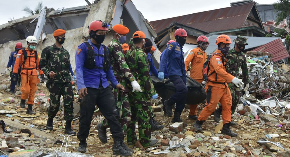 Rescuers move the body of a victim to a mortuary in Mamuju city on January 16, 2021, a day after a 6.2-magnitude earthquake rocked Indonesia's Sulawesi island.