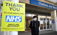 A veteran wearing a Royal Hospital Chelsea hat, and in PPE (personal protective equipment) of a face mask, as a precautionary measure against COVID-19, stands outside the Chelsea and Westminster Hospital in London on April 28, 2020, ahead of a minute's silence to honour UK key workers, including Britain's NHS (National Health Service) staff, health and social care workers, who have died during the coronavirus outbreak.