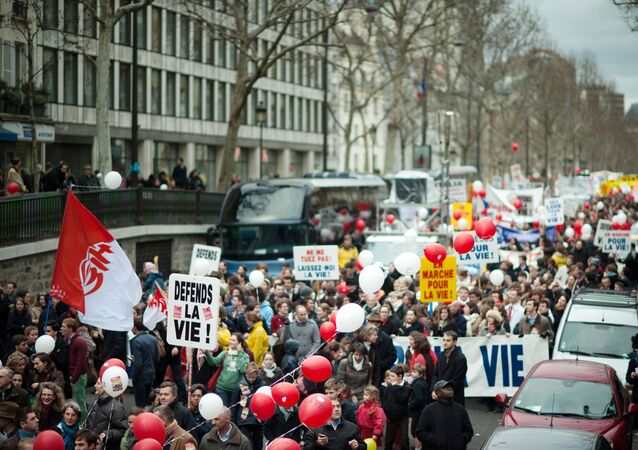 Anti-abortion demonstrators protest on January 22, 2012 in Paris, during the 8th march organised by anti-abortion associations The board foreground reads ! Defend life !.