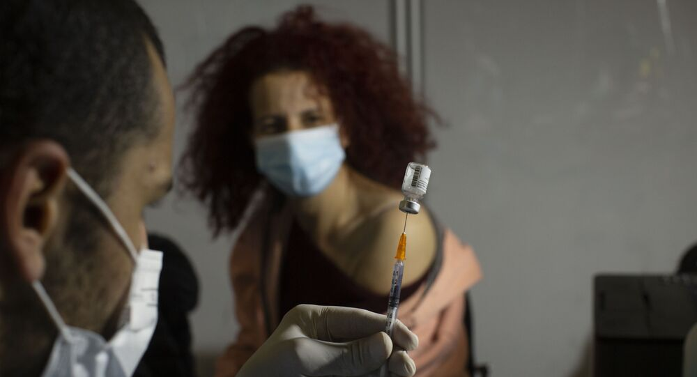 A medical professional prepares to administer the Pfizer COVID-19 vaccine to a woman at a makeshift vaccination center in a sports arena in Jerusalem, Thursday, Jan. 14, 2021.