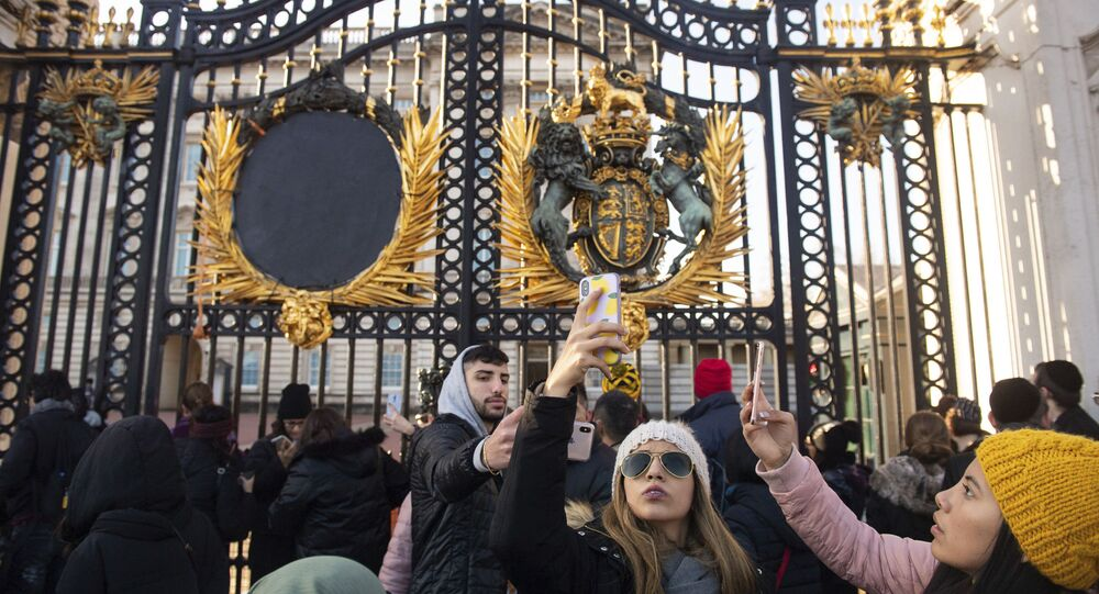 Tourists take photos outside the gates of Buckingham Palace, following a statement by Britain's Queen Elizabeth II and Buckingham Palace, in London, Sunday Jan. 19, 2020