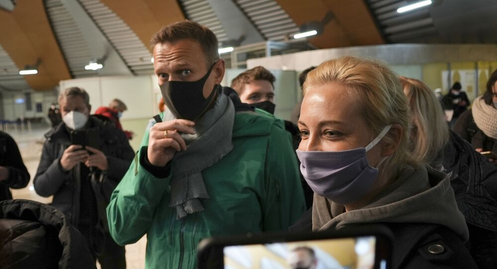 Alexei Navalny and his wife Yuliastand in line at the passport control after arriving at Sheremetyevo airport, outside Moscow, Russia, Sunday, Jan. 17, 2021. Russia's prison service says opposition leader Alexei Navalny has been detained at a Moscow airport after returning from Germany.