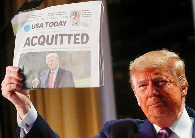 U.S. President Donald Trump holds up a copy of USA Today's front page showing news of his acquittal in his Senate impeachment trial, as he arrives to address the National Prayer Breakfast in Washington, U.S., February 6, 2020