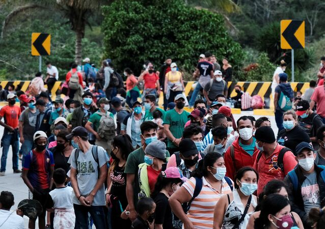 Hondurans taking part in a new caravan of migrants, set to head to the United States, queue to receive water from the Red Cross after arriving to the El Florido border crossing point with Guatemala, in El Florido, Honduras January 15, 2021.